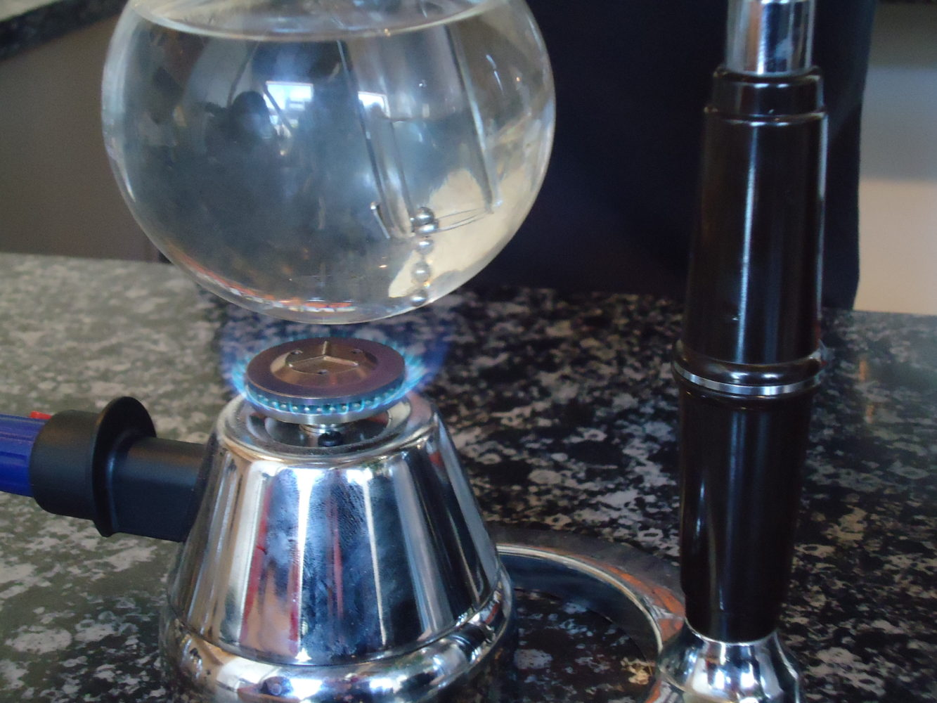 Coffee siphon with gas flame lit on cafe counter