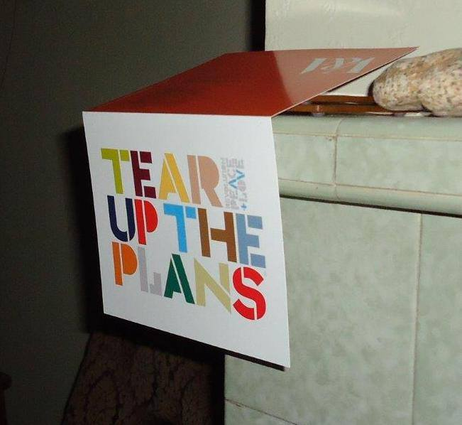 "Greetings card featuring the words ""Tear Up The Plans, Peace & Love"" hanging from a tiled mantle piece"